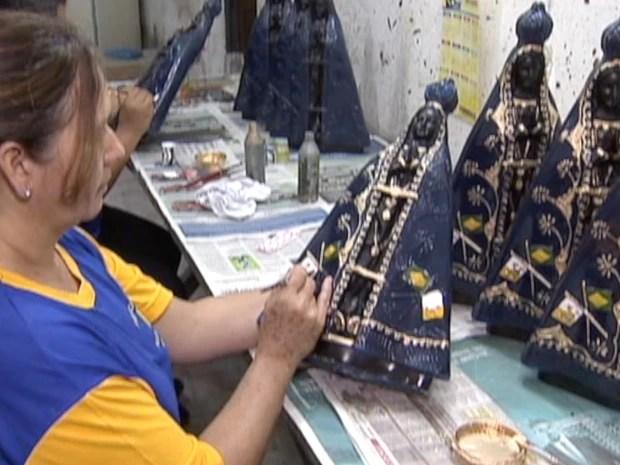 Pequenas fábricas contratam para suprir demanda na saída de imagens de Nossa Senhora, em Aparecida. (Foto: Reprodução/TV Vanguarda)
