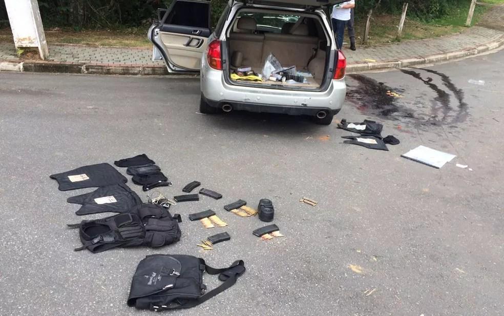 Local do tiroteio em Guararema, com coletes de criminosos apreendidos e poça de sangue ao lado de carro onde estavam assaltantes que foram mortos em troca de tiros — Foto: Giba Bergamin/ TV Globo