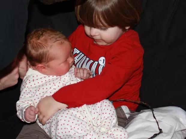 Jack segura seu irmão Alfie ainda lingado à placenta (Foto: BBC)