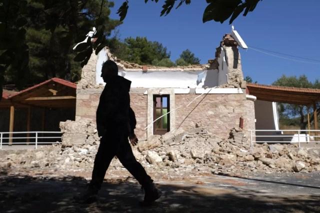 Homem caminha ao lado de capela ortodoxa grega danificada na vila de Arcalochori, na ilha de Creta, após forte terremoto no sul da Grécia em 27 de setembro de 2021 — Foto: Harry Nikos/AP