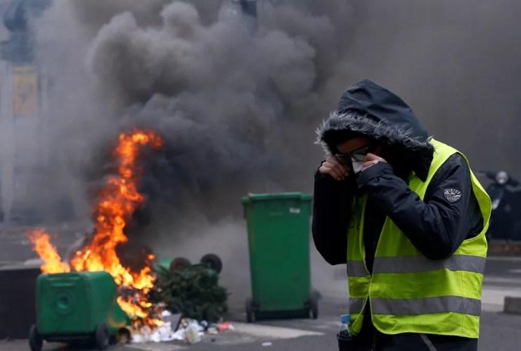 Manifestante protege o rosto da fumaça durante confrontos com a polícia em Paris, no sábado (8). — Foto: Stephane Mahe/Reuters