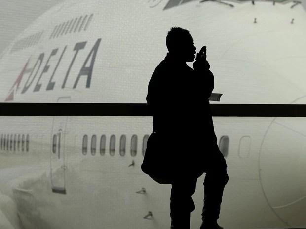 Passageiro fala ao celular antes de embarcar em voo (Foto: Charlie Riedel/AP)