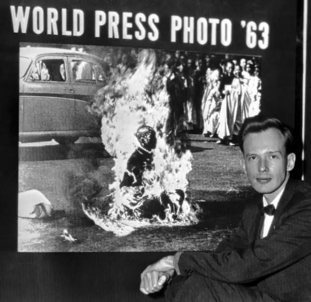O fotógrafo posa com a imagem de sua autoria após receber prêmio do World Press Photo de 1963 em Haia, Holanda (Foto: AP/Arquivo)