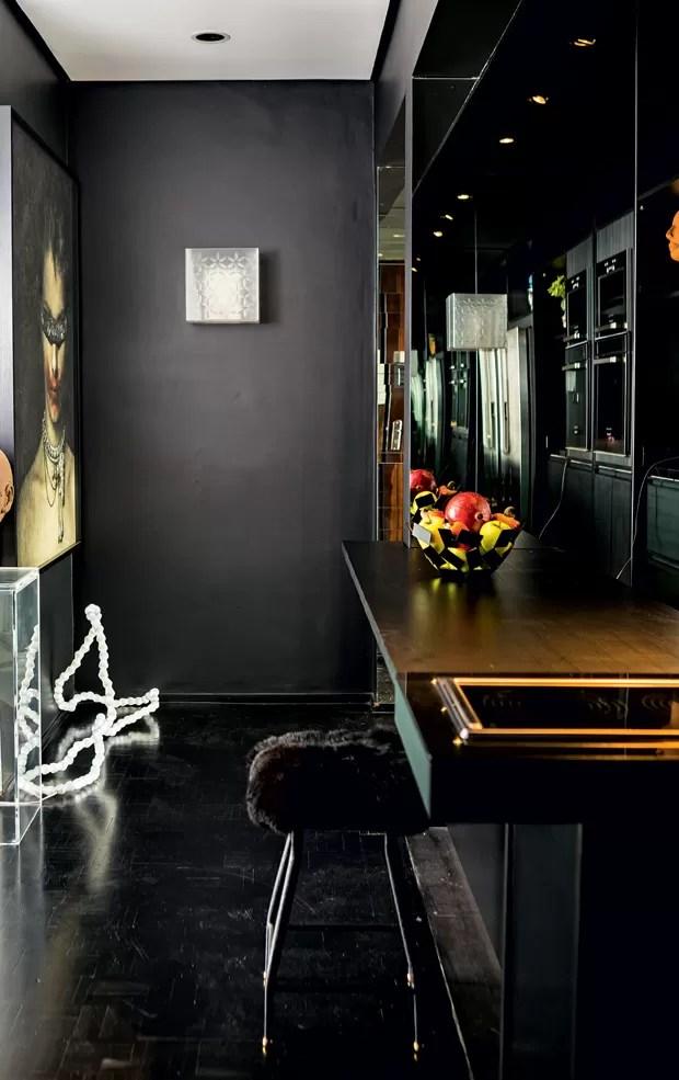 O impacto é imediato com paredes e piso pretos. Ganham destaque a luminária escultura italiana dos anos 1970 e a fotografia de Rodrigo Ribeiro, da Galeria Nuvem (Foto: Edu Castello/Editora Globo)