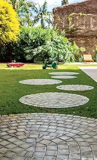 Caminho | As pisadas esféricas foramcriadas com a pedra Hijau, da Palimanan. Spots da Luminare. No fundo, jabuticabeira com borda de clúsias e guaimbês (Foto: Edu Castello/Casa e Jardim)