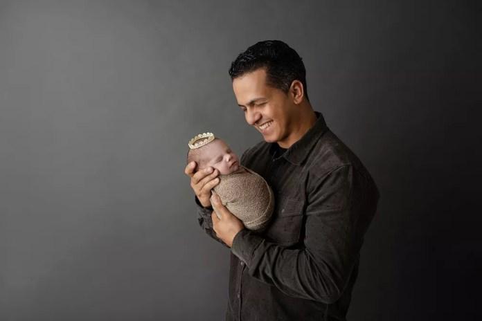 Papai Ailton Maia carrega Arya em ensaio newborn, inspirado na produção da HBO — Foto: Adriana Margotto
