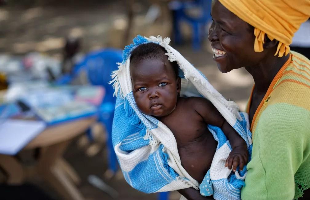 5 de junho - Betty Sakala, refugiada do Sudão do Sul, ri após ver uma foto de sua filha Mary, de 2 meses, enquanto espera que Mary seja examinada em uma clínica de saúde móvel administrada pelo Comitê Internacional de Resgate em Bidi Bidi, em Uganda (Foto: Ben Curtis/AP)