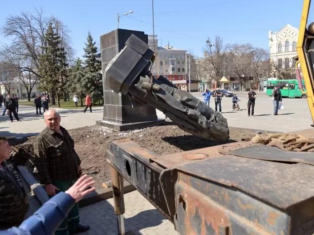 Moradores de Kharkiv removem estátua em homenagem a Nikolai Rudnev, construída em honra à extinta União Soviética (Foto: Sergei Bobok/AFP)