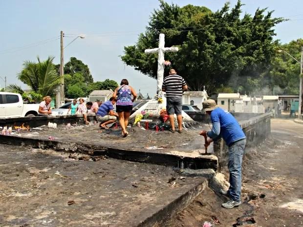 Funcionário de cemitério precisou colocar areia em cima de foco para apagar chamas (Foto: Adneison Severiano/G1 AM)