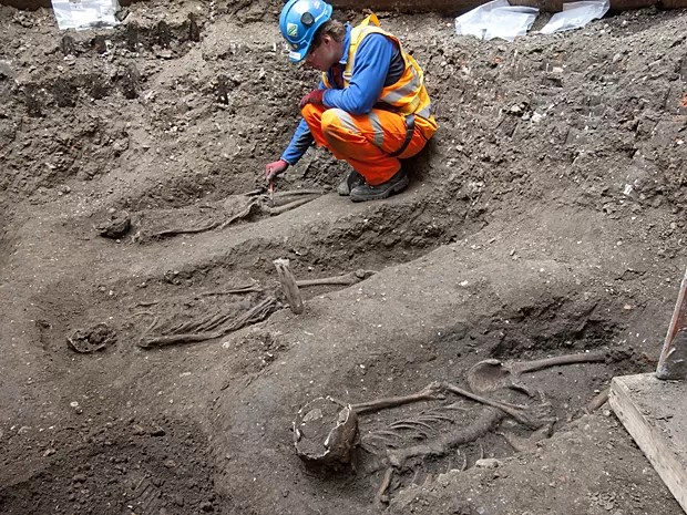 Arqueólogo faz medições de esqueleto encontrado no centro de Londres (Foto: Crossrail/AFP)