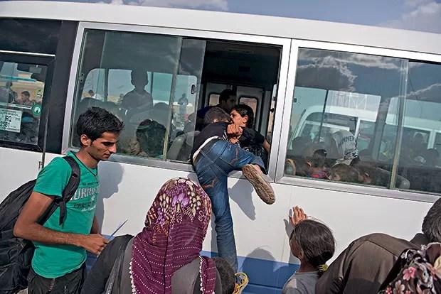 ADEUS AO INFERNO 1. Mulher puxa a filha para dentro de ônibus na Síria, com destino ao Iraque (Foto: Lynsey Addario/The New York Times)
