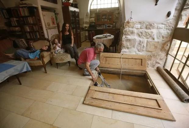 Tal mostra o alçapão no chão de sua sala, que leva até o banheiro de 2 mil anos descoberto no subterrâneo, em Jerusalém (Foto: Gali Tibbon/AFP)