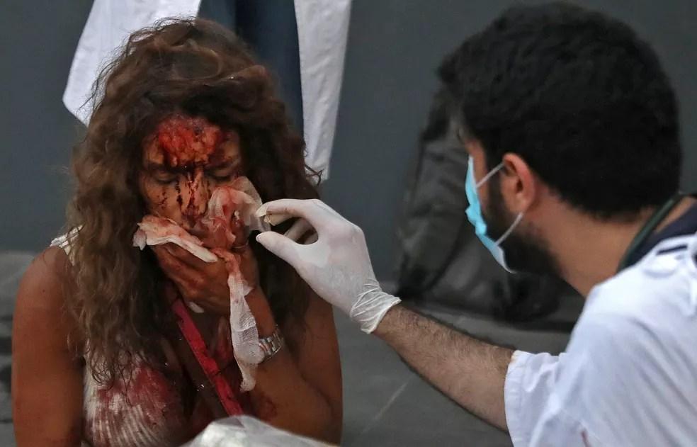 Enfermeiro cuida de mulher ferida em explosão na zona portuária de Beirute, no Líbano — Foto: IBRAHIM AMRO/AFP