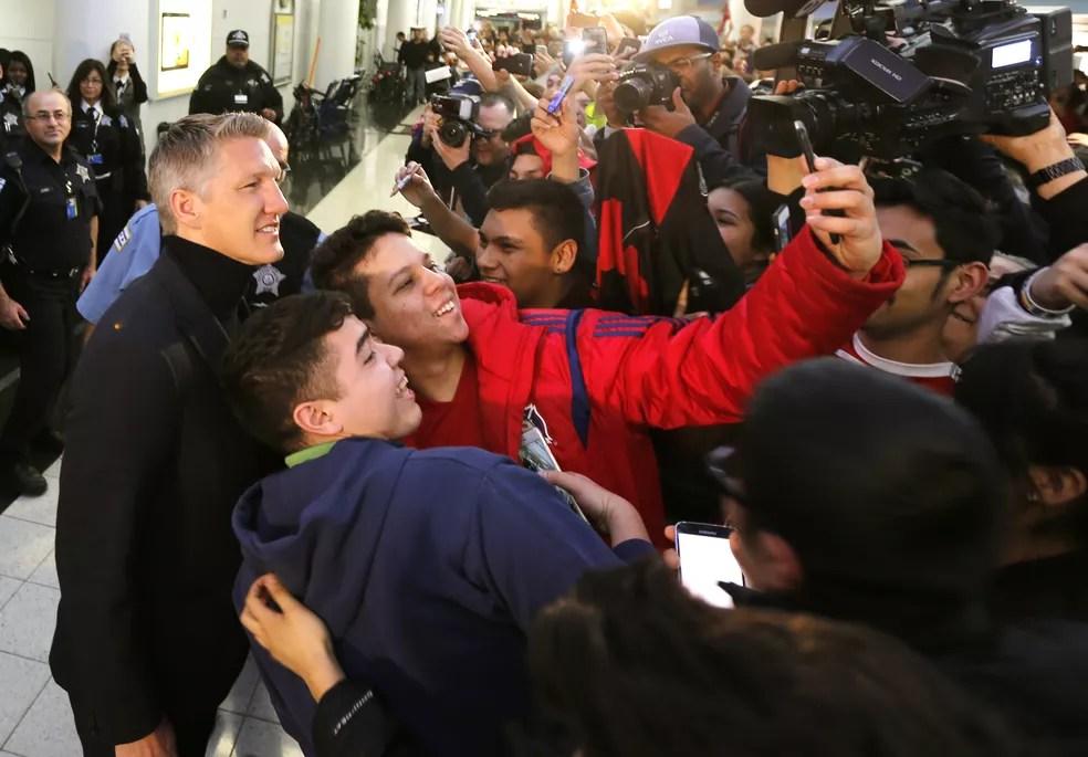 Selfies e mais selfies: Bastian Schweinsteiger deu atenção aos torcedores em chegada a Chicago (Foto: AP )