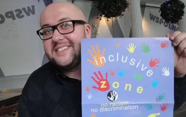 """Jacek Purski, diretor da """"Nigdy Wiecej"""",  mostra cartaz contra racismo (Foto: Rafael Maranhão / Globoesporte.com)"""