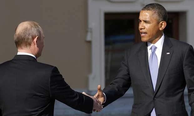 O presidente dos EUA, Barack Obama, à direita, estende a mão para o presidente da Rússia, Vladimir Putin, na chegada para a reunião do G20 (Foto: Alexander Zemlianichenko/ AP)