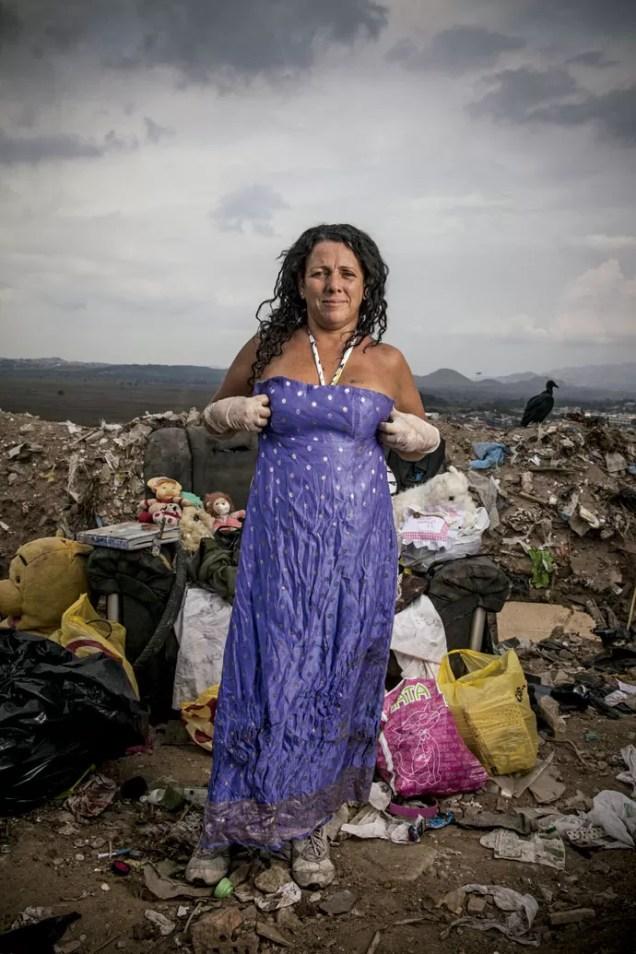 """ENTRE VESTIDOS E URSINHOS DE PELÚCIA - Os companheiros de Gericinó não têm muitas lembranças de Andreia Rodrigues, 40 anos. Ela só aparecia aos domingos, acompanhada do marido e do sogro, para procurar roupas e ursinhos de pelúcia. Um tipo de passeio ao shopping, sem a urgência dos catadores que tinham de ganhar a vida. As roupas, ela usaria fora do lixão após um processo de restauração. """"Levo para casa, lavo bem, e a roupa fica como nova"""", ela diz. Assim que os catadores receberam a indenização do poder público e a catação foi oficialmente encerrada, ninguém mais soube dela.   (Foto: Micha Ende)"""