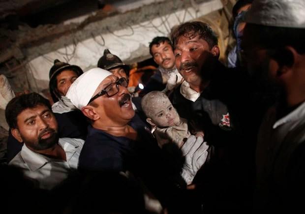 Criança resgatada com vida dos escombros (Foto: Vivek Prakash/Reuters)