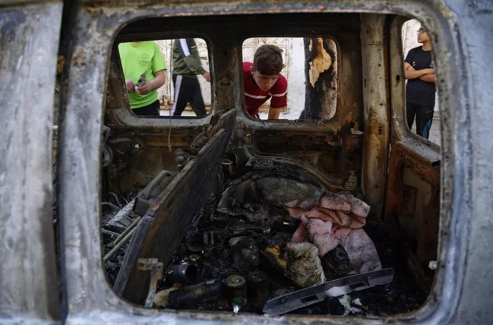 Crianças palestinas olham para carro destruído após ser atingido em ataque aéreo israelense na Cidade de Gaza na quarta (19) — Foto: Hatem Moussa/AP