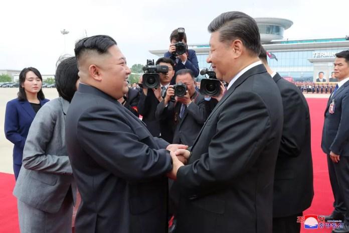 Kim Jong-un e Xi Jinping se cumprimentam no aeroporto de Pyongyang, na Coreia do Norte — Foto: KCNA via Reuters
