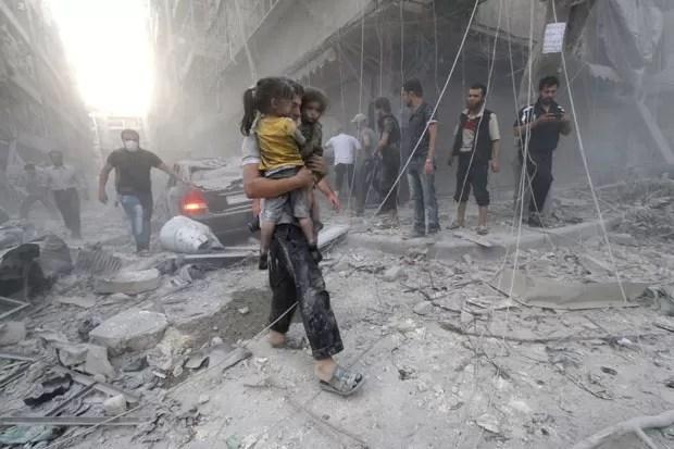 Sírio carrega duas meninas cobertas de poeira após ataque aéreo em área rebelde em Aleppo nesta quarta-feira (9) (Foto: Zein Al-Rifai/AFP)