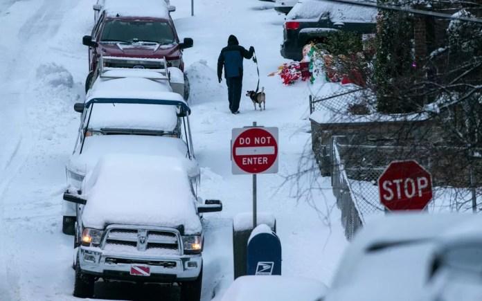 Homem passeia com cachorro por ruas cobertas de neve na Filadélfia, Pensilvânia, na quinta-feira (17) — Foto: Alejandro A. Alvarez/The Philadelphia Inquirer via AP