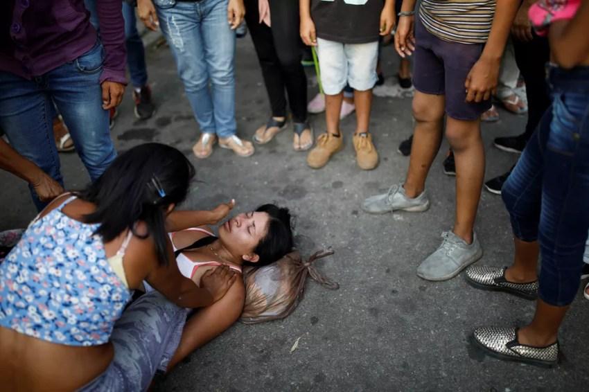 Parente de preso em centro de detenção em Valencia, na Venezuela, passa mal após notícia sobre incêndio (Foto: Carlos Garcia Rawlins/Reuters)