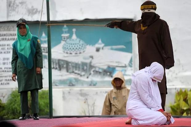 Jovem foi punida nesta segunda-feira (17) a 23 chibatadas porque foi vista muito próxima de seu namorado em Banda Aceh (Foto: Chaideer Mahyuddin/AFP)