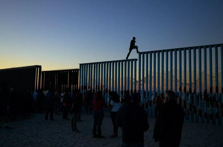 Um homem hondurenho caminha pelo topo do muro na fronteira que separa o México e os Estados Unidos, em Tijuana, no México — Foto: Gregory Bull/AP
