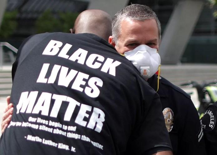 Um manifestante abraça um policial durante um protesto do lado de fora da sede da polícia de Los Angeles, na Califórnia, nesta terça-feira (2), contra a morte de George Floyd  — Foto: Lucy Nicholson/Reuters