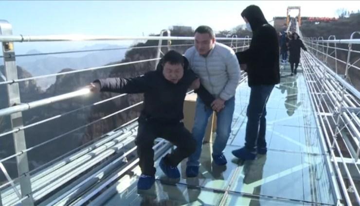 Homem caminha sobre a ponte de vidro mais longa da China (Foto: Reprodução/Reuters)