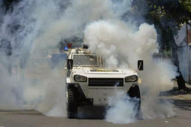 Carro blindado da polícia tenta dispersar manifestantes durante protesto contra o presidente venezuelano, Nicolás Maduro, em Caracas, nesta quinta-feira (20) (Foto: Federico Parra / AFP)