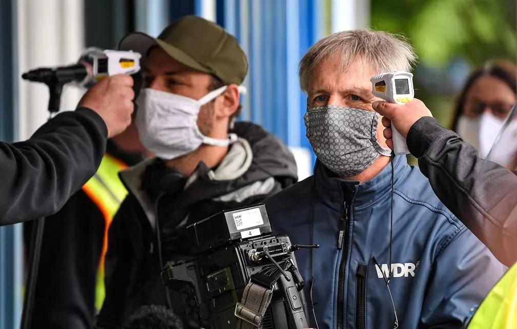 Segurança controla temperatura de jornalistas na entrada da fábrica da Ford em Colônia, na Alemanha. Montadora norte-americana reinicia a produção nesta segunda-feira (4)  — Foto: Martin Meissner/AP