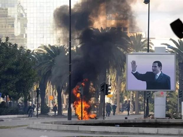 Manifestantes enfrentam forças de segurança na Tunísia nesta sexta (14) próximo à cartaz com foto do presidente Zine El Abidine Ben Ali, que deixou o país (Foto: AFP)