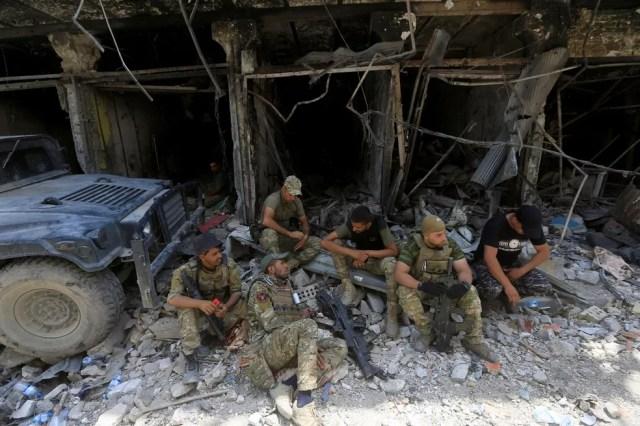 Membros da Divisão Especial de Emergência iraquiana descansam na cidade velha de Mossul neste domingo (9) (Foto: REUTERS/Alaa Al-Marjani)