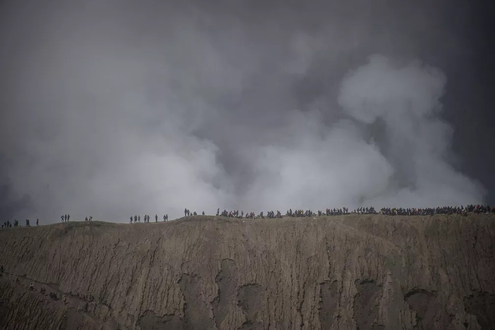10 de julho - Turistas e membros da tribo Tengger escalam o monte Bromo durante o festival Yadnya Kasada em Probolinggo, na Indonésia. Os membros da tribo que vivem ao redor do monte do vulcão Bromo-Semeru jogam oferendas na cratera para homenagear Sang Hyang Widhi, Deus Todo Poderoso, durante o 14º dia do mês kasada baseado no tradicional calendário lunar hindu (Foto: Juni Kriswanto/AFP)