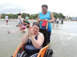 Talita, aluna de Mogi, canta e bate palmas no mar, em Bertioga. (Foto: Pedro Carlos Leite/G1)