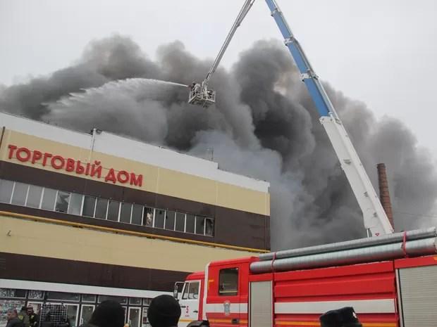 Bombeiros combatem incêndio em centro comercial de Kazan, na Rússia, na quarta-feira (11) (Foto: AP Photo/Ministério Russo de Situações de Emergência)