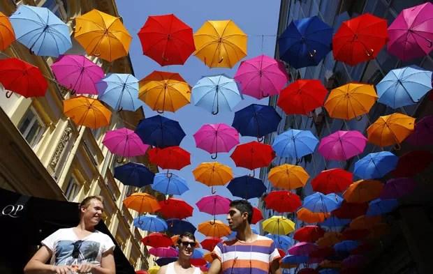 Com a temperatura alcançando os 40º C nesta segunda-feira (29) na Sérvia, uma rua coberta com guarda-chuvas de diferentes cores virou refúgio no centro da capital Belgrado (Foto: Marko Djurica/Reuters)