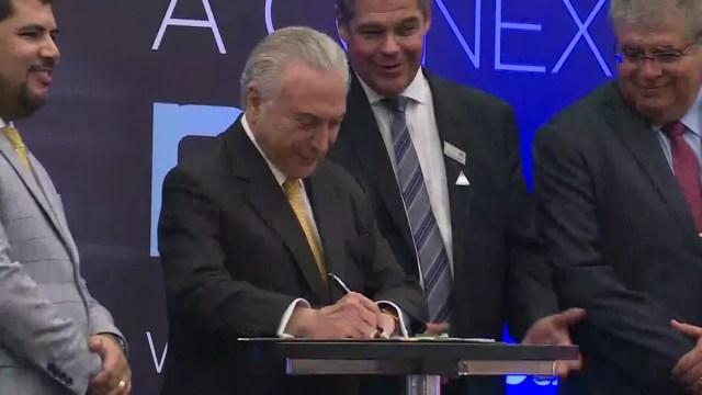 O presidente Michel Temer assina decreto que regulamenta medida provisória no Salão Internacional do Automóvel em São Paulo — Foto: Reprodução/TV Globo