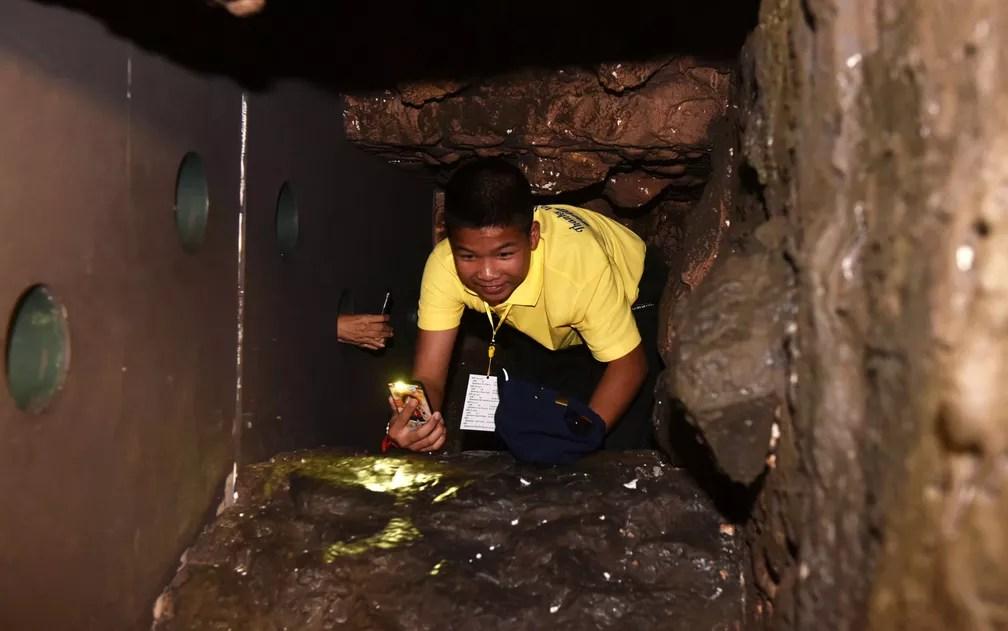 Phanumas Saengdee, um dos integrantes do time 'Javalis Selvagens', rasteja por réplica da caverna onde ficou preso em uma exposição interativa montada em Bangcoc, na Indonésia, na quinta-feira (6) (Foto: Panumas Sanguanwong/Thai News Pix/AFP)