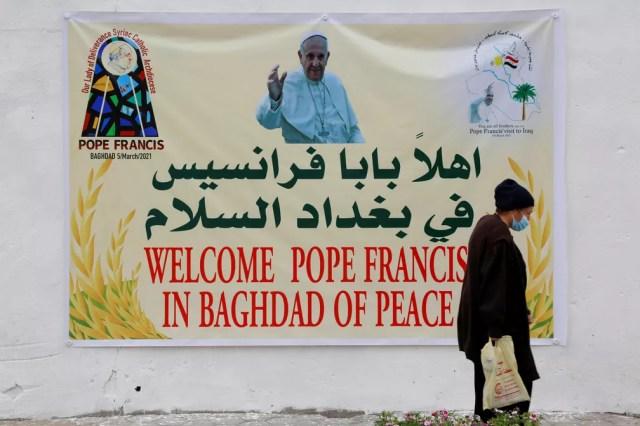 Mulher caminha perto de pôster que dá boas-vindas ao Papa Francisco em Bagdá em 4 de março  — Foto: Reuters/Teba Sadiq