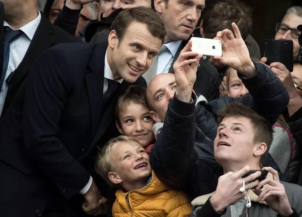 Candidato Emmanuel Macron posa para uma selfie com apoiadores depois de votar em Le Touquet  (Foto: PHILIPPE HUGUEN / AFP)