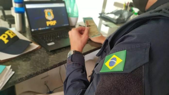 Agente da PRF analisa CHN falsa encontrada com homem — Foto: PRF/Divulgação