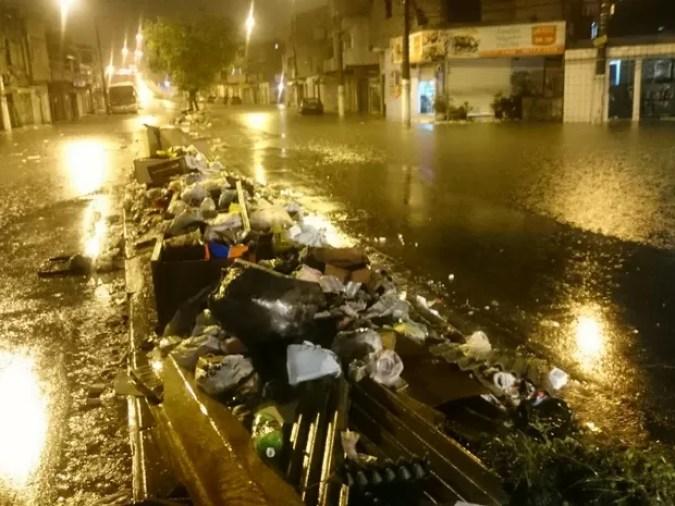 Lixo acumulado em meio à rua alagada na avenida Nações Unidas (Foto: G1)