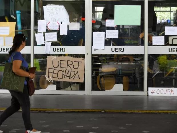 Uma mulher passa por um prédio da Universidade Estadual do Rio de Janeiro ocupado por estudantes. As aulas, paralisadas há 21 dias, serão retomadas nesta quarta-feira (16) (Foto: Tânia Rego/Agência Brasil)
