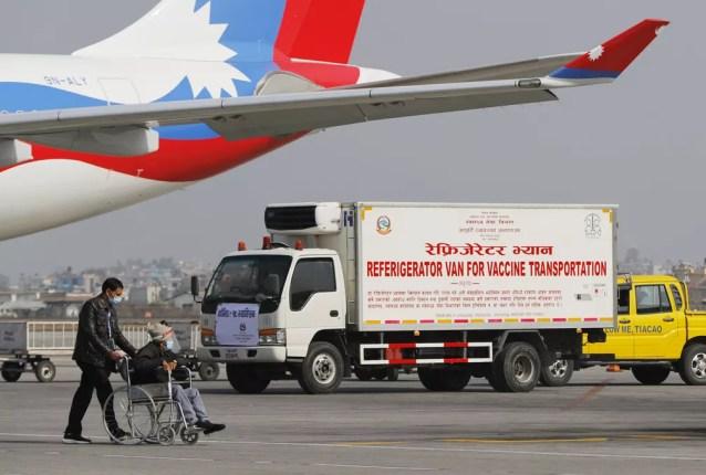 Van aguarda no aeroporto internacional de Catmandu para transportar as doses da vacina de Oxford/AstraZeneca contra a Covid-19 que a Índia doou para o Nepal — Foto: Niranjan Shrestha/AP
