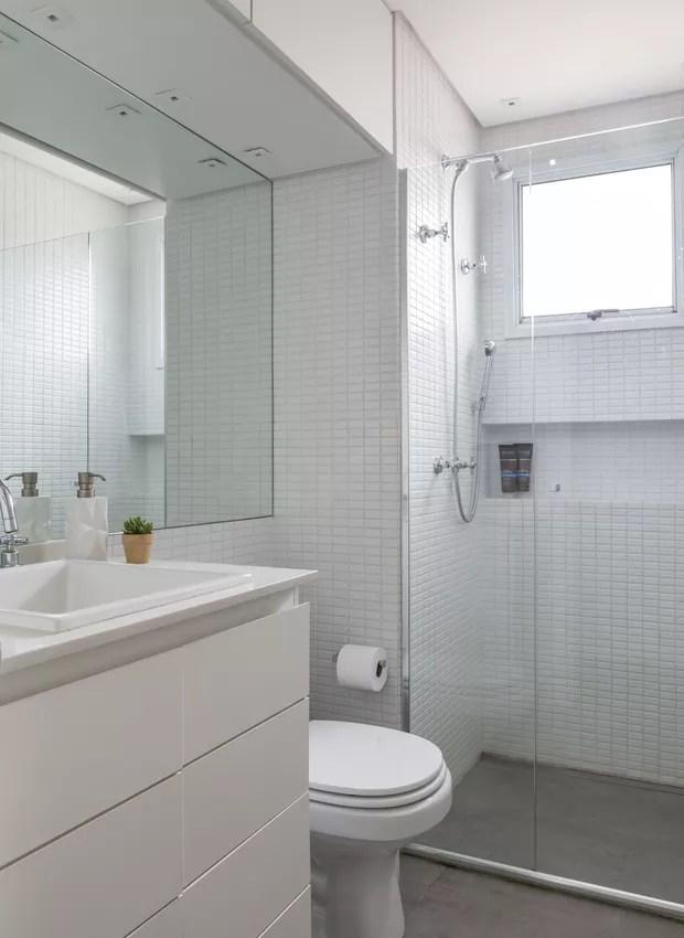 Porcelanato com cor de cimento reveste o piso, enquanto pastilhas brancas cobrem as paredes do banheiro. Repare que o nicho dentro do boxe vai de canto a canto, reservando bastante espaço para itens de beleza (Foto: Evelyn Müller/Divulgação)