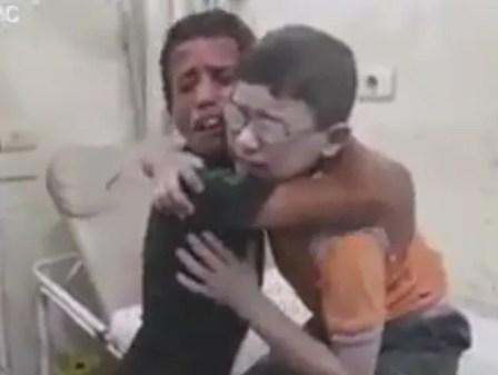 Meninos se reencontram após bombardeio em Aleppo, no norte da Síria, matar o irmão deles (Foto: AMC/ Reprodução G1)