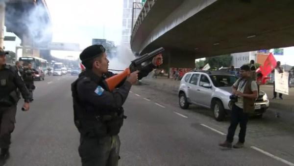 Rio de Janeiro, 7h37: PM saca arma não letal na frente de uma bomba de efeito moral contra manifestantes — Foto: Reprodução/TV Globo